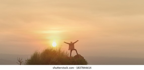 Abstract success with silhouette of peple standing on top of mountain and raise hands at sunraise sky background