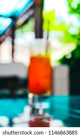 Abstract summer cafe bar lounge blurred background, a glass with orange juice on a terrace.