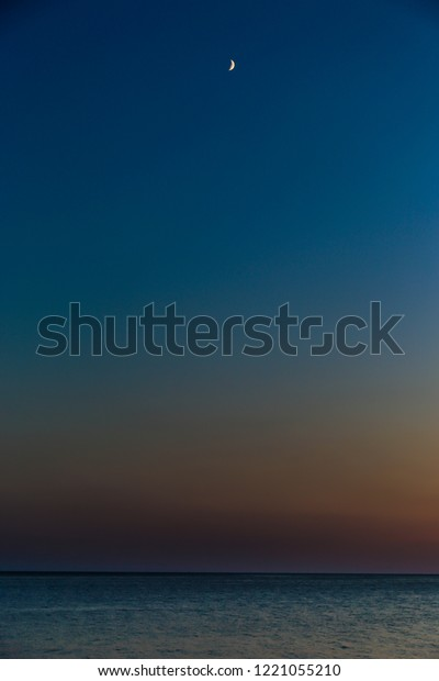 Abstract Sunset at sea with visible moon