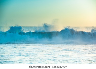 Abstract sunset seascape background. Crashing Pacific Ocean sea waves in beautiful soft yellow sunsetting light on California beach, USA. Pale pastel teal to Tiffany blue greens of water and skies