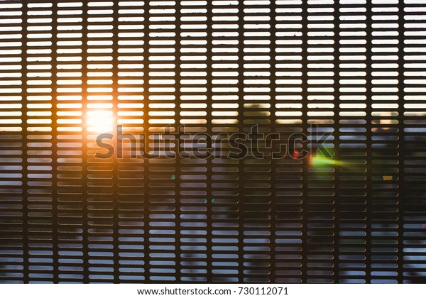Abstract sunset shines through a metal screen at a train station.