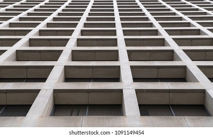 Abstract of a tall building front wall. The pattern is formed by squares. It is a low angle view.