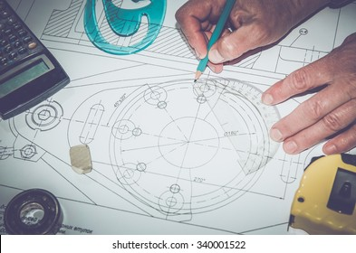 Abstract technical drawings. Mechanical engineer at work.  Pencil, calculator, line and hand man. Paper with technical drawings. tinted photo