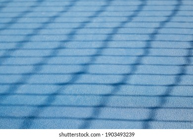 Abstract tennis court texture. Defocused tennis net shadow on ground, outside early morning. Blue rubberized and granulated ground surface for shock absorption. Tennis sport backdrop texture.