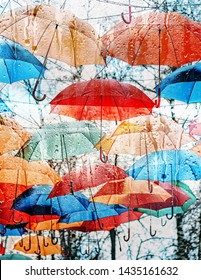 abstract texture of autumn umbrellas and wet glass. fall season. colorful umbrellas over rainy window. rain outside window on rainy, autumn day.