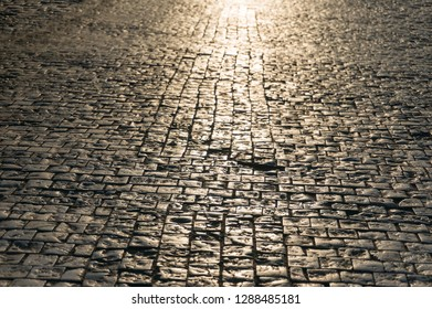 Abstract texture, background of sunlit stone road cobbles