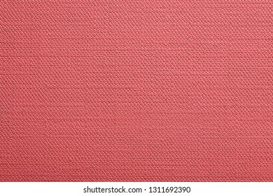 abstract texture of paper or other material with stamping closeup for a fashionable background or for wallpaper of living coral color