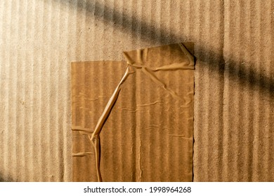 Abstract texture of a wrinkled cellotape on a brown cardboard box carton