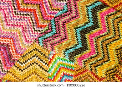 Abstract textured background of multicolored zigzag woven raffia material