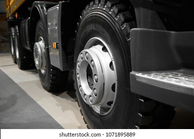 Abstract tipper truck wheels and tires with blured background. Truck wheel rim. Truck chassis exhibit on car Exhibition. Commercial transport with special truck wheels mud tires