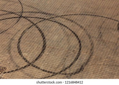 Abstract transport background with pivoting black tire track over asphalt road surface. Trace of drift, braking rubber tire, black track. Abstract road background with intersection of tires from drift