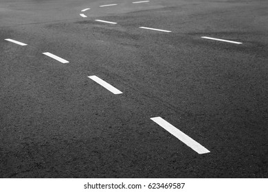 Abstract transportation background. White bent striped dividing lines over dark rough asphalt, road marking. Selective focus with shallow DOF
