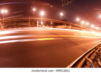 Abstract transportation photo: road (street, highway) at night with a bridge (flyver, overpass, interchange), traffic headlight trails and street lamps (lights)