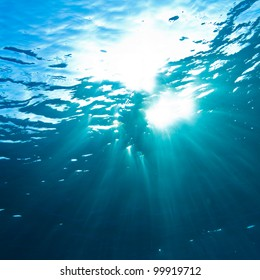 abstract underwater scenery sunrays going through water surface in deep blue sea