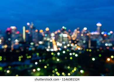 Abstract urban night light bokeh defocused of city and the office building. City and tower blurred background on twilight color sky. Night light of real estate as concept.