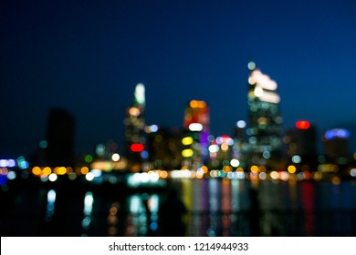 Abstract urban night light bokeh defocused background and fisher in Saigon river. Twilight blurred light office building with bokeh background in Sai Gon/ Saigon (Ho Chi Minh City) Vietnam