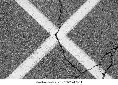 Abstract urban white x with crack. Asphalt blacktop with white painted x.