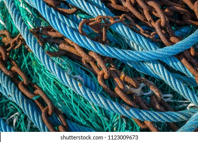 Abstract of various blue, green ropes and rusty chains lying on a fishing boat