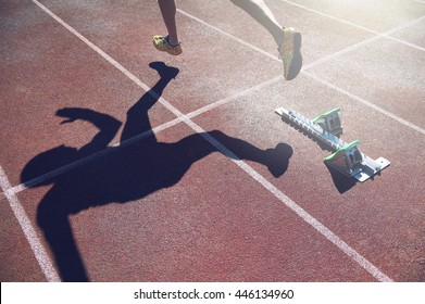 Abstract view of athlete in gold shoes sprinting from the starting line blocks of a race on a red running track