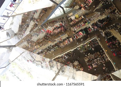 Abstract view from below of a mirror surface located above an outdoor public place. Reflective board showing confused shapes with people and rows in a market. Confusing lines and mixed things.