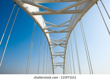 Abstract view of bridge support against a blue sky.