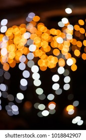 Abstract view of bright, blurred fairy lights against dark background