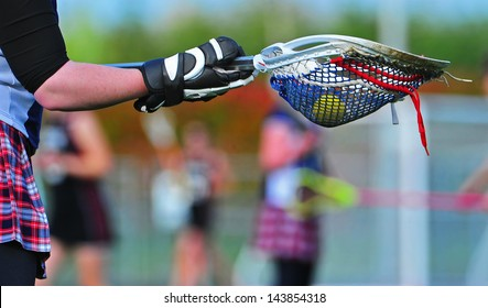 Abstract view from the goal of a girls lacrosse game as the goalie prepares to pass the ball to one of her team mates.