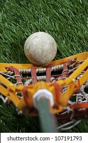Abstract view of a lacrosse stick scooping up a ball on a green turf field.