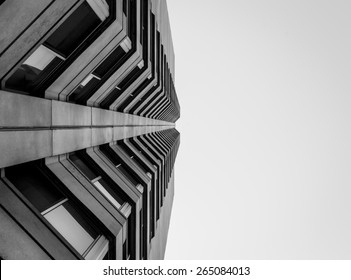 Abstract view looking up at modern concrete and glass building. Artistic view of exterior architectural design and detail. A modern office building with abstract color background.