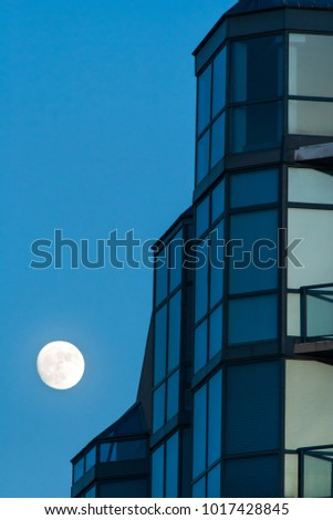 abstract view of modern skyscraper at full moon night