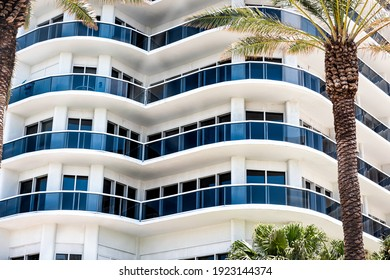 Abstract view on residential apartment complex building with many windows, balconies painted in white blue on sunny day with palm trees
