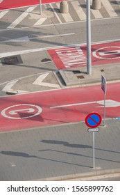 An abstract view of road signs and red painted pavement signs on a port road in Barcelona, Spain.