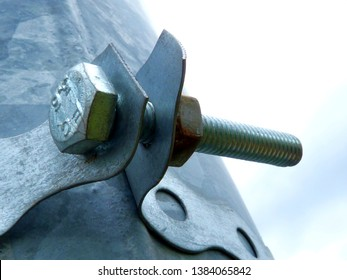 abstract view of silver metallic and gray zink colored perforated steel fastener strip clamp and fastening bolt around galvanized steel pipe lamp post detail. security concept.