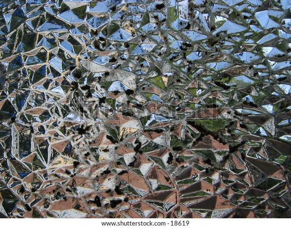 Abstract view through a fancy glass window with various colours from a garden scene showing as fragments.