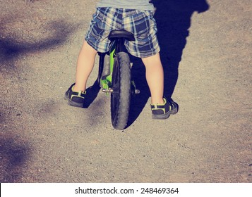 abstract view of toddler riding bike on gravel path with retro instagram filter (shallow depth of field - focus is on planted foot)
