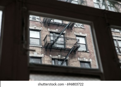 An abstract view trough a window of a classic fire escape ladder on a brownstone building in Manhattan.