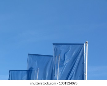 abstract view of waving light blue flags in strong wind on silver color metal poles under blue sky.  For blue sky scenario or blue sky concept.