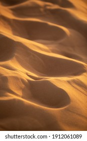 Abstract view of wind blown patterns with shallow depth of field of sand dunes in late afternoon low sunlight in red sand dunes near Dubai