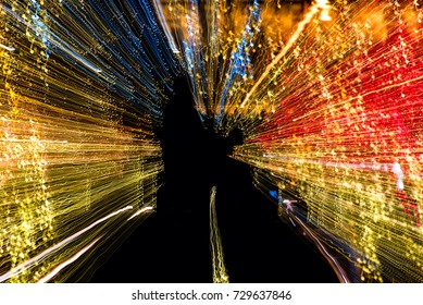 Abstract view of zoomed Christmas lights streaming around a public statue in silhouette
