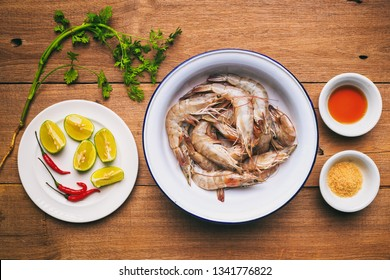 Abstract vintage photography of prepared raw shrimp or prawn with Thai style ingredient for spicy salad, traditional Thai food on wooden table, selected focus.