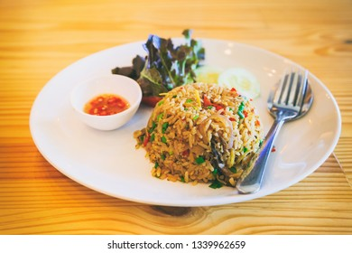 Abstract vintage photography of spicy fried rice, traditional Thai food on wooden table, selected focus.
