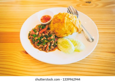 Abstract vintage photography of stir fried minced pork and basil with egg top on rice, traditional Thai food on wooden table, selected focus.