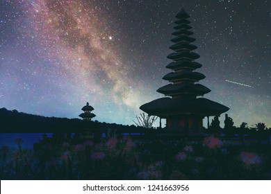 Abstract vintage tone long exposure photography of Pura Ulun Danu temple on the lake Beratan in Bali, Indonesia in the night time with milky way and stars on the night sky background.