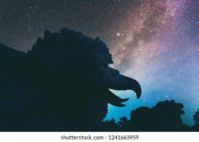 Abstract vintage tone long exposure photography of Garuda statue at the Garuda Wisnu Kencana Cultural Park in Bali, Indonesia in the night time with milky way and stars on the night sky background.