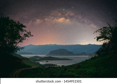 Abstract vintage tone long exposure photography of The Lake in Uttaradit, Thailand in the night time with milky way and stars on the night sky background.
