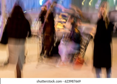 Abstract vintage tone motion, blurred image of street musicians and spectators, night urban street life, motion blur concept, for background use