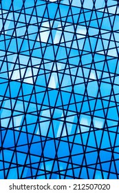 Abstract of a wall of windows in various shades of blue, silver and white