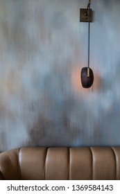 Abstract wallcovering in multicolor, blue and gray brush pattern with wall lamp in weathered brushed metal and beige leather sofa / Interior Design / Graphic Design / Background texture