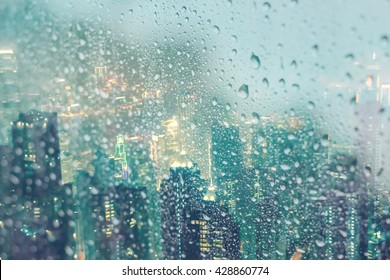 Abstract of water droplets on mirror with city night background in raining day
