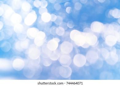 abstract white Bokeh circles Christmas on blue background, glitter light Defocused